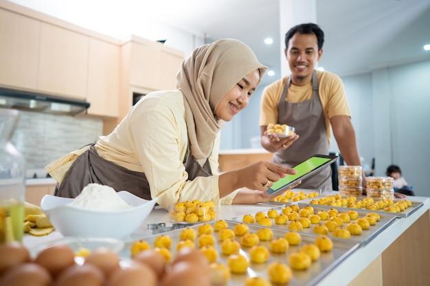 Muslimische paargeschäftsverkäufer, die essen zu hause bestellen, zusammen nastar ananaskuchen für eid mubar
