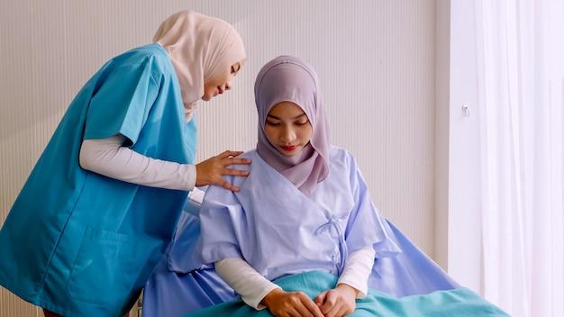 Muslimische physiotherapeutin, die sich um patientin im krankenzimmer kümmert.