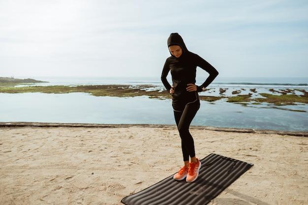 Muslimische sportfrau am strand, die ausübt