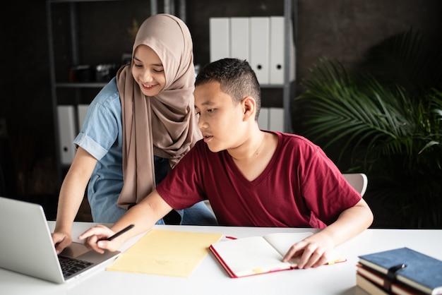 Muslimische studenten, die gemeinsam papierarbeiten erledigen