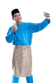 Muslimischer asiatischer mann, der ein bild von sich selbst macht. selfie über weiß