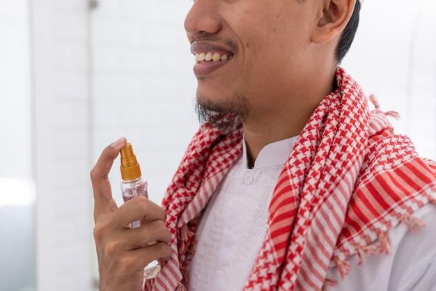 Muslimischer asiatischer mann, der sich auf eid mubarak vorbereitet. zieh dich an und trage parfüm auf seinen körper auf