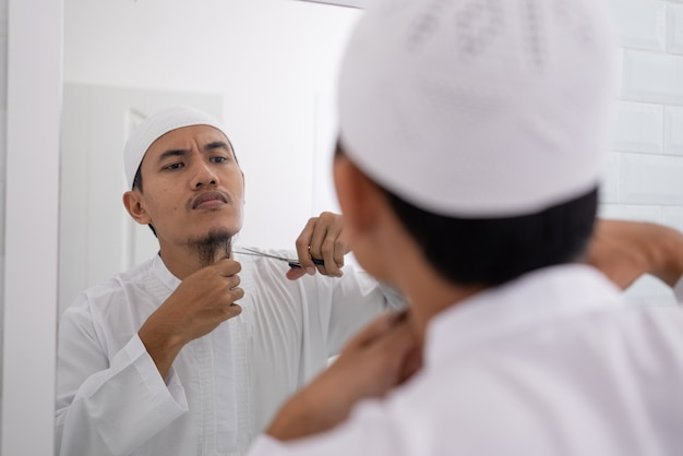 Muslimischer asiatischer mann, der sich nicht sicher ist, seinen bart mit einer schere zu rasieren