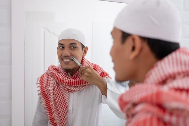 Muslimischer asiatischer mann, der spiegel betrachtet und sich anzieht, bevor er zur moschee geht