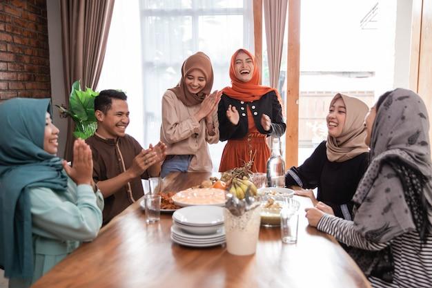 Muslimischer freund und familie lachen beim mittagessen zusammen