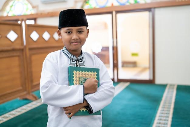 Muslimischer junge, der heiligen koran hält