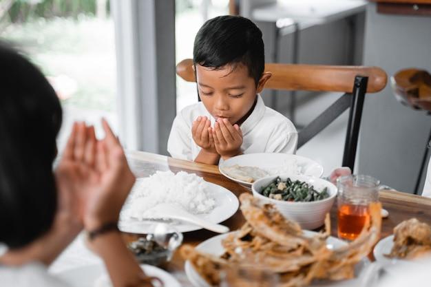 Muslimischer junge, der vor dem essen betet