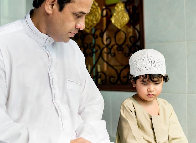 Muslimischer junge, der wie zu salah lernt