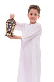 Muslimischer junge mit laterne, die ramadan feiert