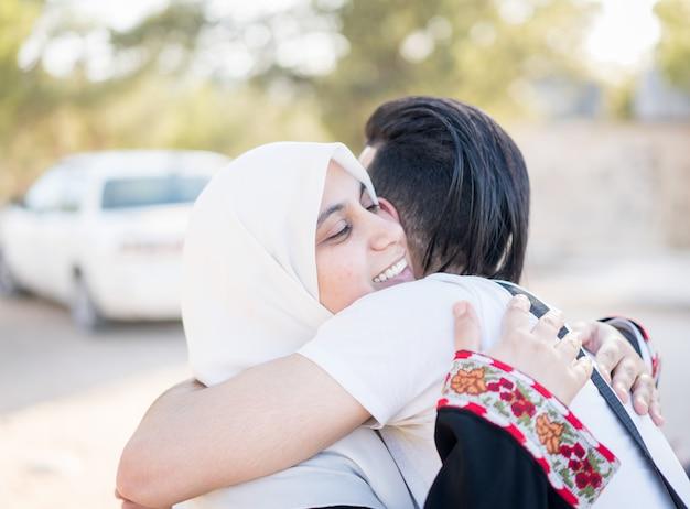 Muslimischer junger mann, der seine mutter umarmt
