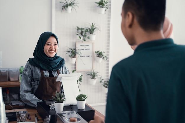 Muslimischer kellner in der kaffeetheke