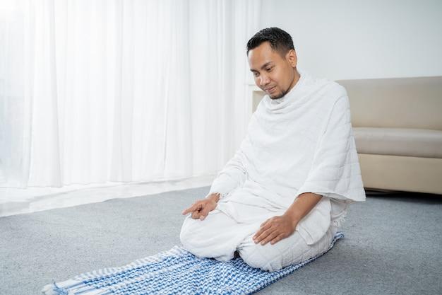 Muslimischer mann betet in weißer traditioneller kleidung ihram