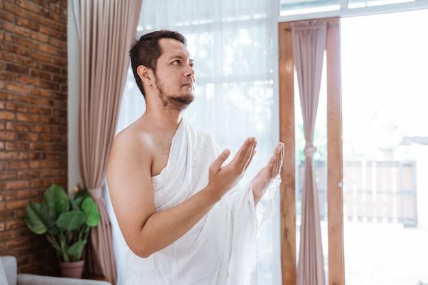 Muslimischer mann, der betet, ihram kleidung tragend