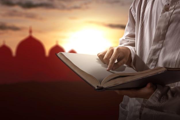 Muslimischer mann, der den koran auf seinen händen liest