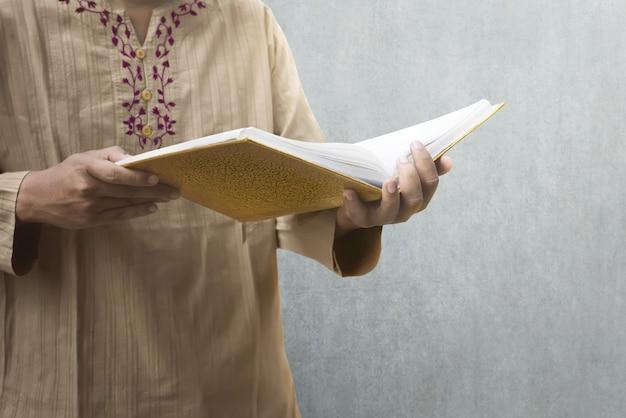Muslimischer mann, der den koran liest