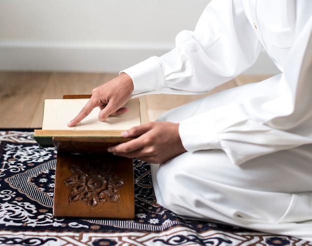 Muslimischer mann, der den koran studiert