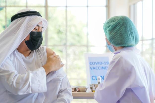Muslimischer mann, der in einer klinik oder einem krankenhaus sitzt, um einen covid-impfstoff zu erhalten, wobei die handkrankenschwester den impfstoff injiziert