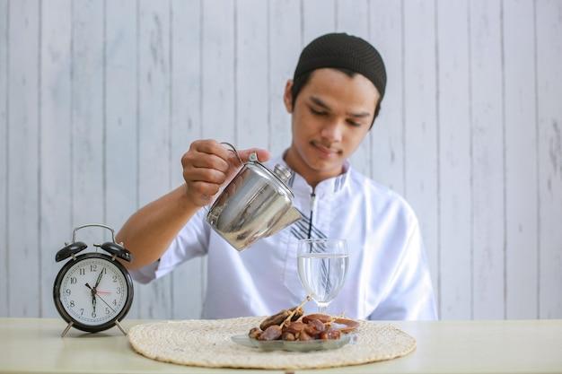 Muslimischer mann, der koko trägt, der wasser in ein glas auf dem tisch für iftar-vorbereitung gießt