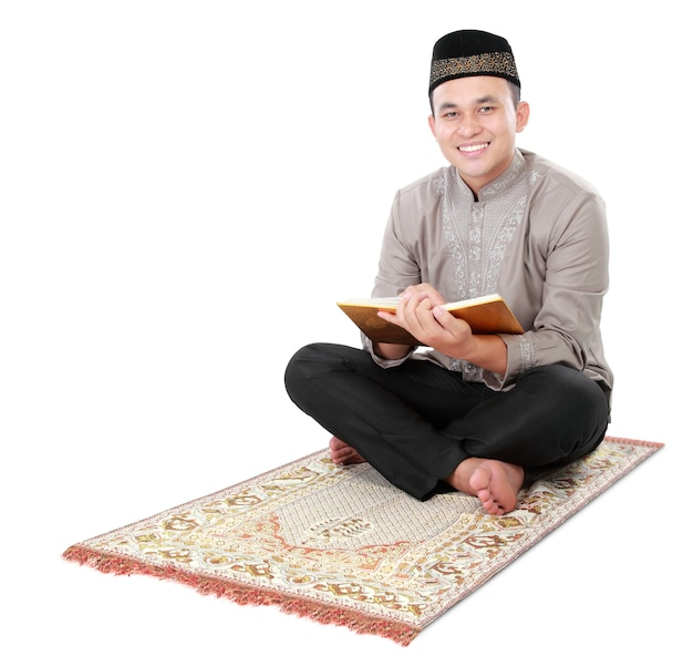 Muslimischer mann, der koran hält und liest