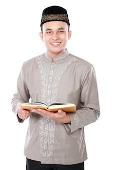 Muslimischer mann, der koran hält