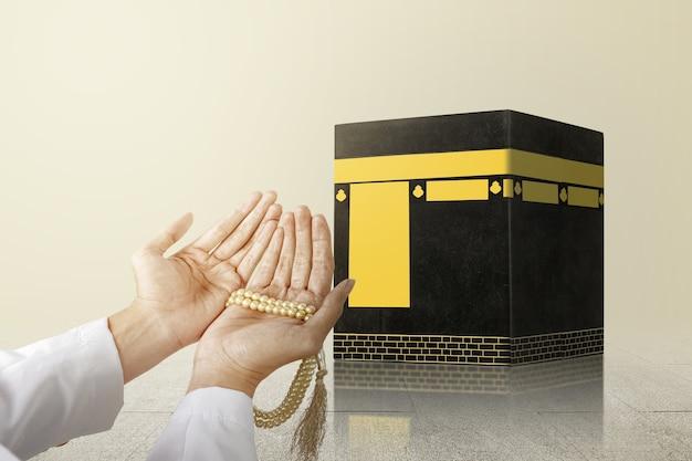 Muslimischer mann, der mit gebetsperlen an seinen händen vor der kaaba mit hellem hintergrund betet