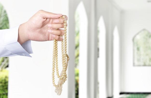 Muslimischer mann, der mit gebetsperlen auf seinen händen betet