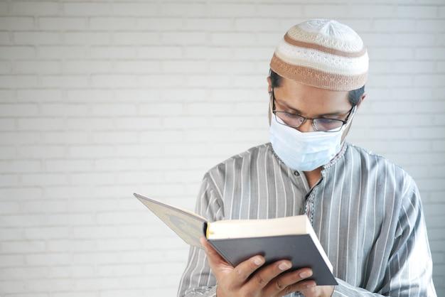 Muslimischer mann mit gesichtsmaske, die stechpalmenbuch des korans innen liest