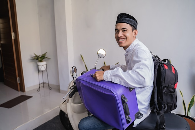 Muslimischer mann reitet motorrad für idul fitri balik kampung mudik, der koffer trägt