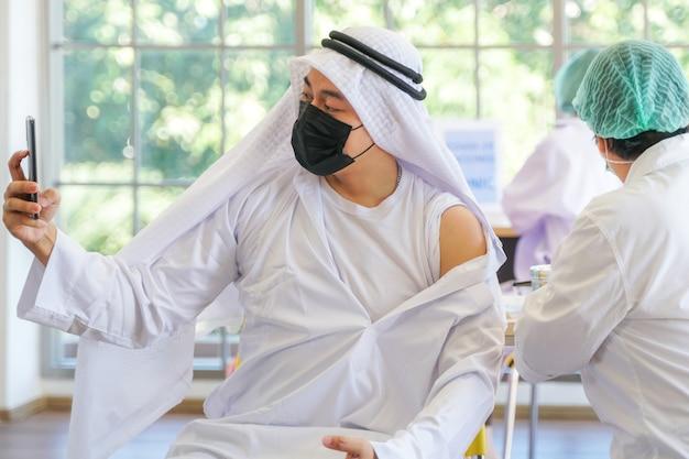 Muslimischer mann selfie per telefon, nachdem er einen covid-impfstoff erhalten hat krankenschwester verwendet handabdeckung gipsarm