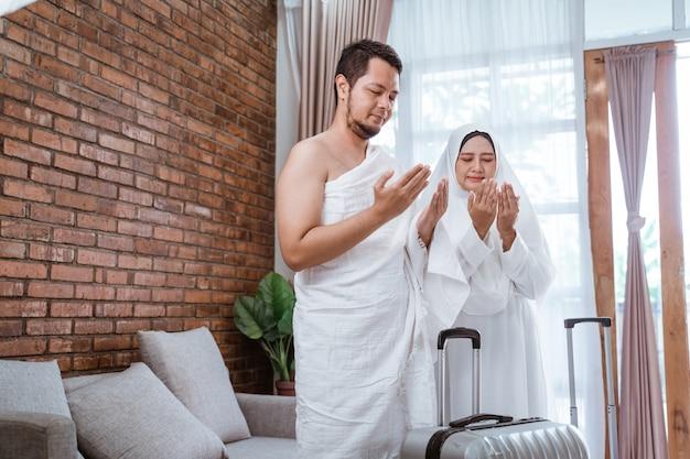 Muslimischer mann und frau, die offenen arm beten