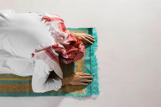 Muslimischer mann verbeugt sich in ehrfurcht vor flachlage