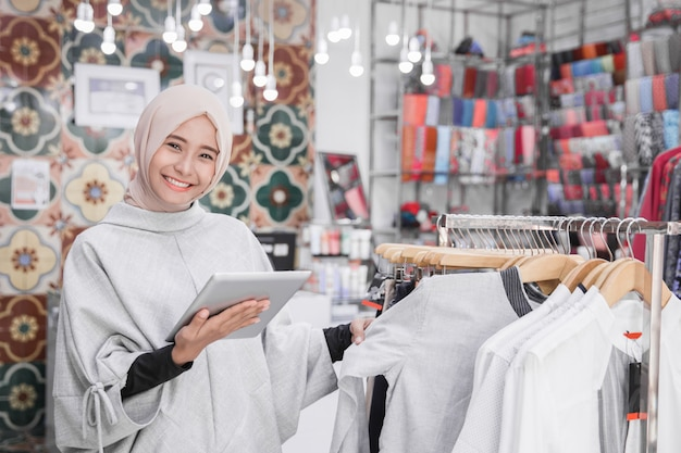 Muslimischer modeboutiquenbesitzer mit tablette