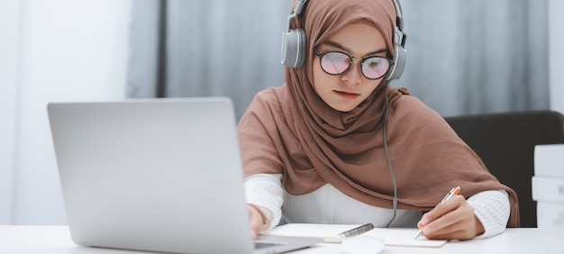 Muslimischer student, der einen laptop für fernunterricht verwendet