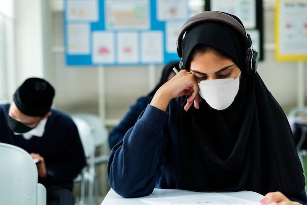 Muslimischer student, der maske trägt, die in einem klassenzimmer studiert