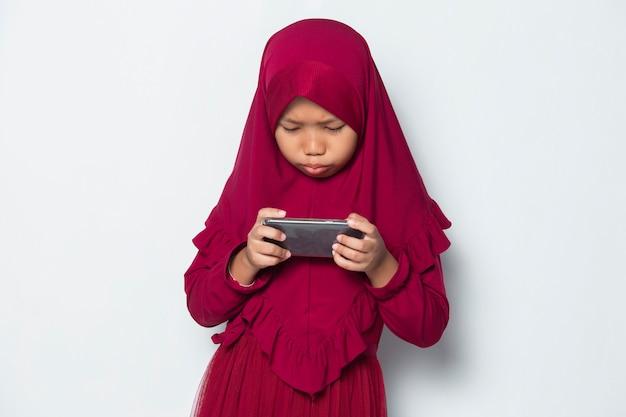 Muslimisches asiatisches kleines mädchen mit smartphone-spiel auf weißem hintergrund
