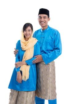 Muslimisches asiatisches paar während hari raya eid mubarak über weißem hintergrund