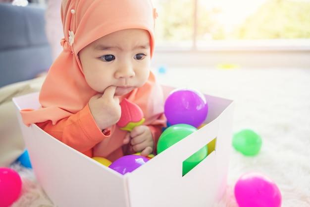 Muslimisches baby spielt mit bunten spielzeugen im wohnzimmer.