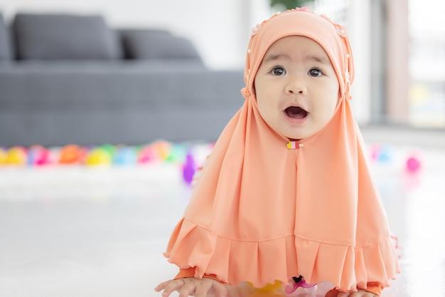 Muslimisches baby spielt mit bunten spielzeugen im wohnzimmer
