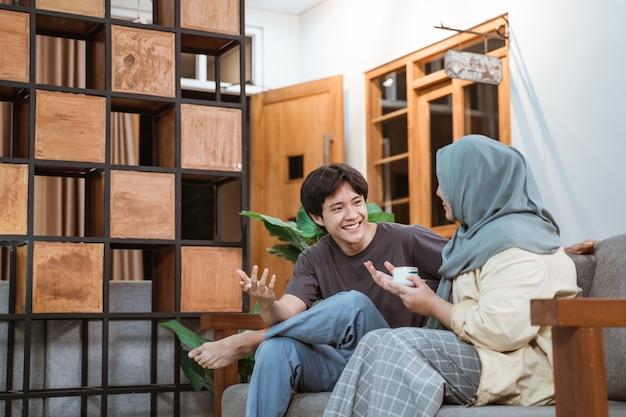 Muslimisches junges paar, das auf sofa im haus plaudert