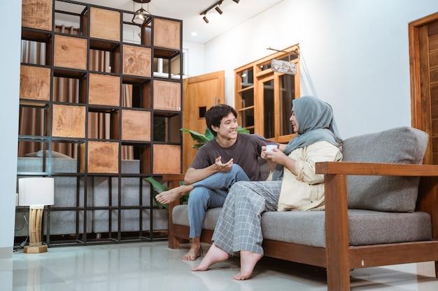 Muslimisches junges paar, das auf sofa im wohnzimmer zu hause plaudert