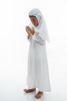Muslimisches kind, das betet und ihram trägt