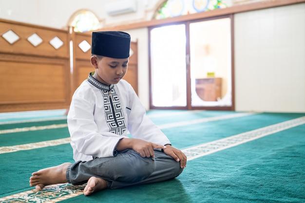 Muslimisches kind, das in der moschee betet