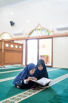Muslimisches kind, das koran liest Premium Fotos