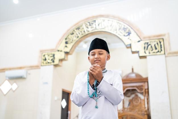 Muslimisches kind, das zu gott betet