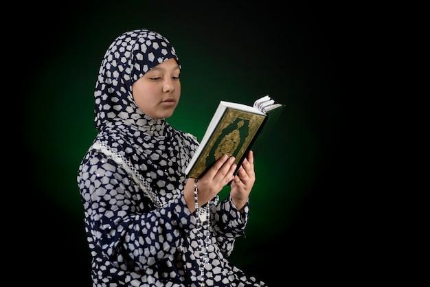 Muslimisches mädchen, das heiliges buch des korans liest