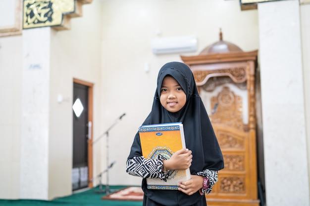 Muslimisches mädchen, das koran hält