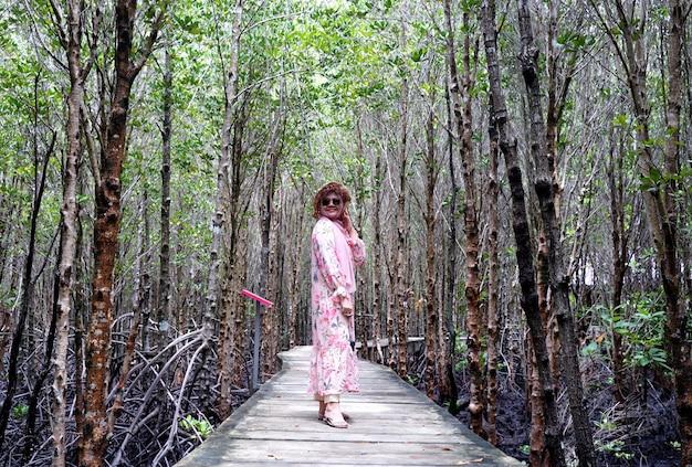 Muslimisches mädchen, das zur kamera lächelt, genießt urlaub am tropischen meer. teenager-mädchen, das sonnenstrohhut und weißes kleid trägt, das auf holzbrücke mit grünem pflanzenhintergrund des mangrovenwaldes steht.