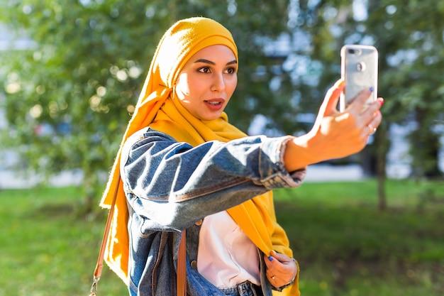 Muslimisches mädchen in hijab macht ein selfie am telefon, das auf der straße der stadt steht