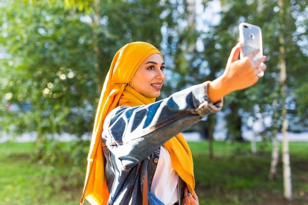 Muslimisches mädchen in hijab macht ein selfie auf dem smartphone, das auf der straße der stadt steht