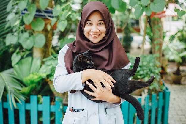 Muslimisches mädchen lächelt mit ihrer schwarzen katze